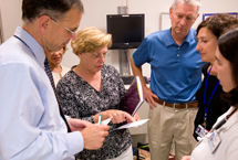 Lloyd Alderson MD reviews brain tumor chemotherapy plan with four people looking on