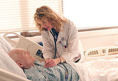 Intensivist Carla Lamb, MD, checks in on a patient in the Medical Intensive Care Unit