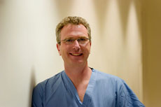 male breast health doctor in blue scrubs with glasses against yellow wall