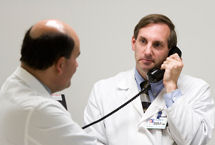 lahey male doctor in white on phone sitting with patient