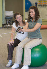 Lahey physical therapist assisting patient with upper body strength exercise