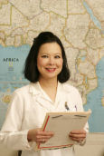 Lahey Hospital Doctor Ooi standing in front of a travel map