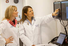 Andrea McKee, MD, and Rebecca Yang, MD, examine a patient's imaging results