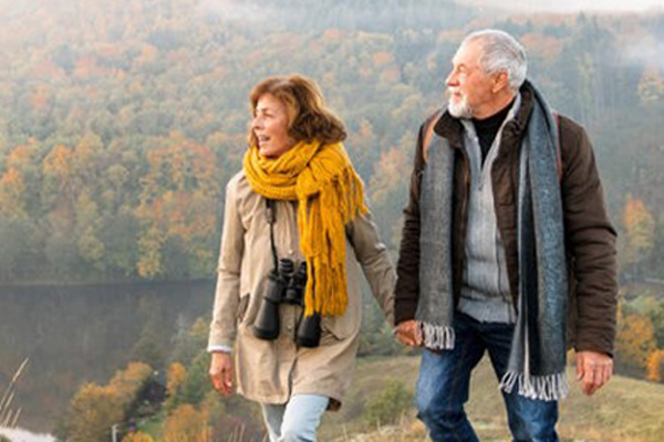 Older couple walking in nature, looking at Lake in fall