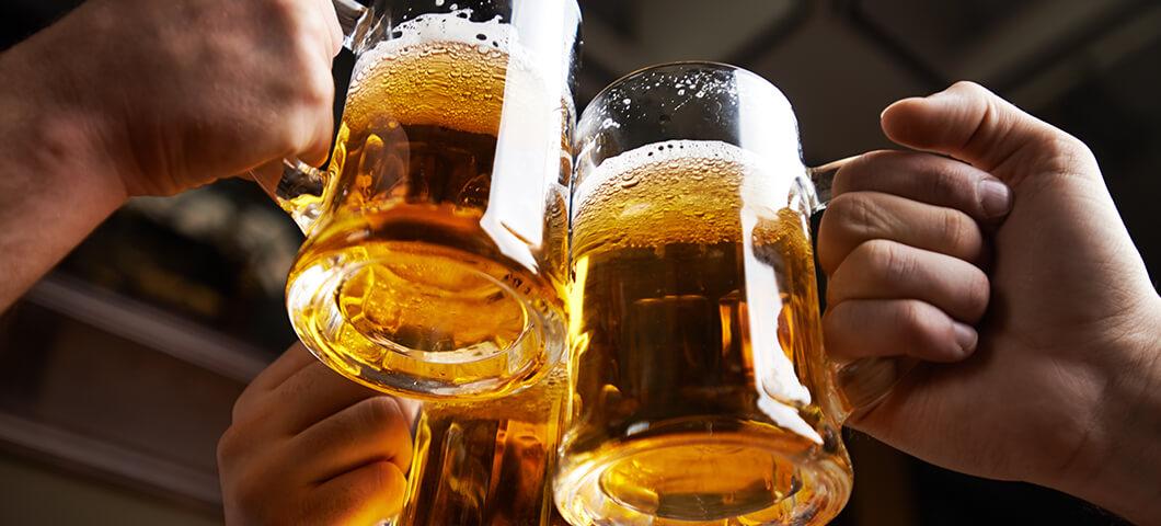 three people cheersin with beer mugs