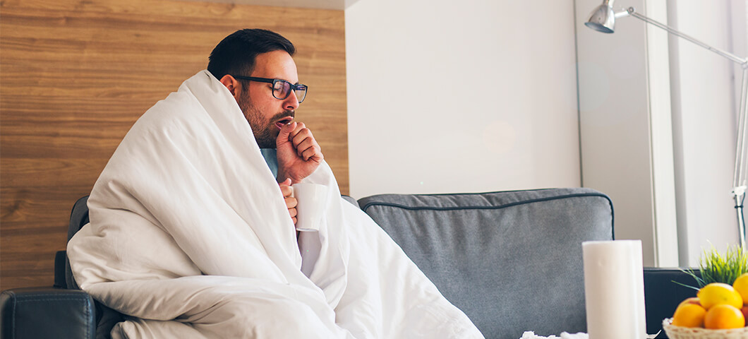 man coughing wrapped up in blanket