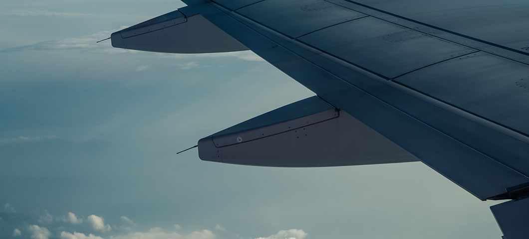 An airplane wing through airplane window with a cloudy sky background