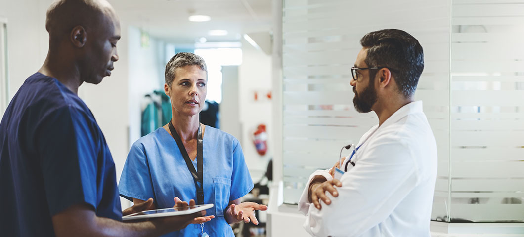 Female doctor discussing with male colleagues