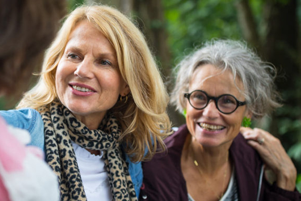 Two older women pictured with friends