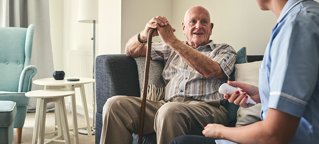 Senior man and female carer sitting on sofa and talking in living room at home